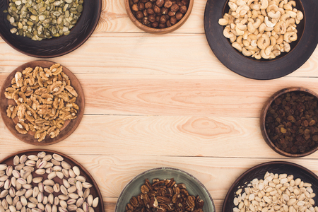 top view of various healthy nuts in bowls on wooden table