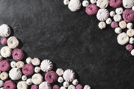 bes en witte marshmallows op zwart tafelblad met kopie ruimte Stockfoto