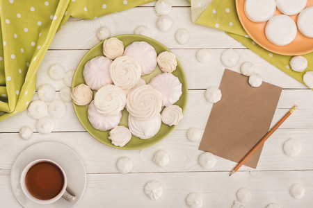 top view of white marshmallows, tea and card on white wooden tabletop with green tablecloth
