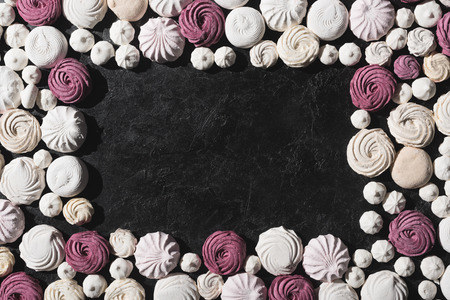 frame of berry and white marshmallows on black tabletop with copy space