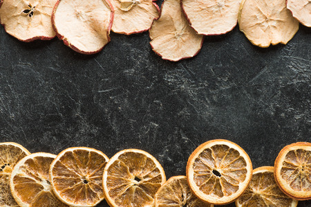 Top view of dried apples and oranges on a dark grungy surface