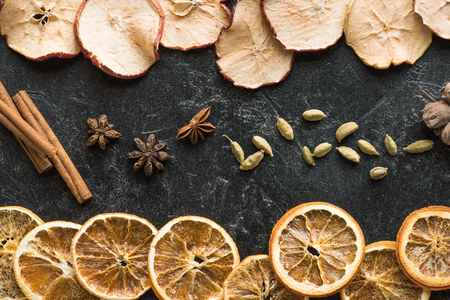 Top view of dried apples and oranges with cinnamon sticks and carnation