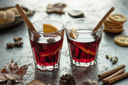 Two glasses of mulled wine with cinnamon sticks on a gray surface