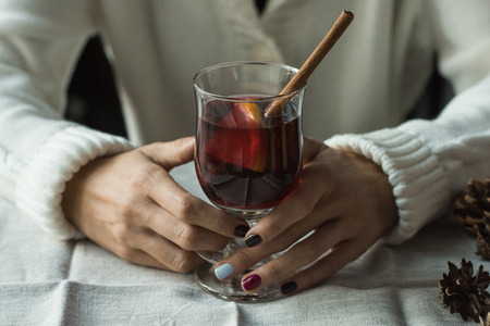 Cropped image of woman sitting at table and holding glass of mulled wine Stock Photo