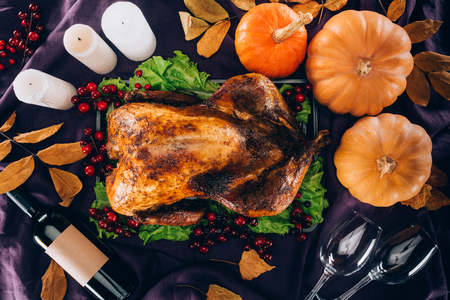 Top view of baked turkey with pumpkins, wine bottle and glasses on violet tablecloth