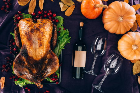 Top view of baked turkey with wine bottle and glasses on violet tablecloth