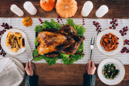 Top view of Cook preparing to cut baked turkey served on a table with knife and fork on thanksgiving day Stock Photo