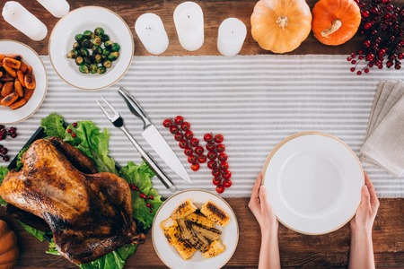 Man putting a plate on a served table with baked turkey for thanksgiving day Stock Photo