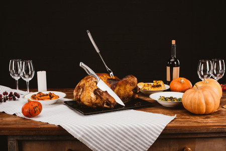 Baked turkey with fork and knife in it on served wooden table for thanksgiving day Foto de archivo