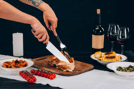 cook cutting baked turkey with fork and knife into pieces on a table Stock Photo