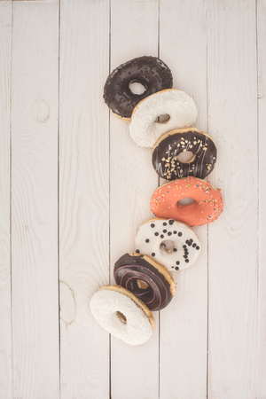 top view of fresh sweet tasty donuts on wooden table top
