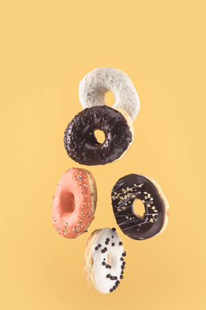 close-up view of fresh delicious doughnuts isolated on yellow