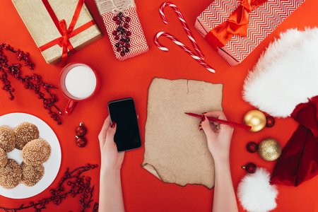 cropped view of woman with smartphone writing on blank papyrus and choosing presents, isolated on red Stock Photo