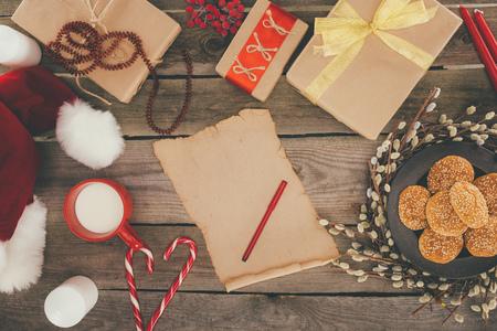top view of cup of milk, blank papyrus, christmas presents on wooden tabletop Zdjęcie Seryjne