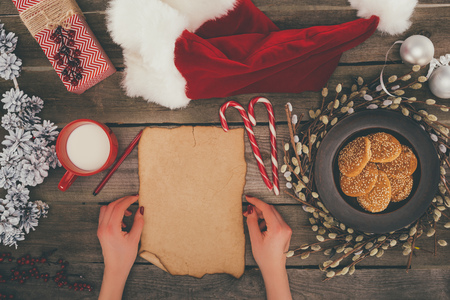 cropped view of woman with blank papyrus and santa hat on wooden tabletop