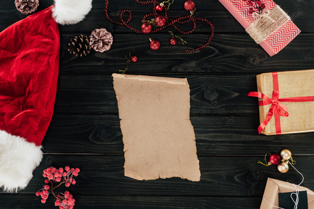 top view of blank papyrus, christmas presents and santa hat on wooden tabletop