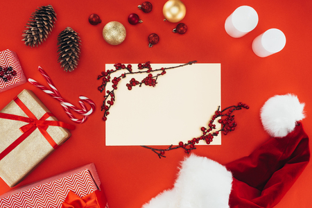 christmastime: top view of blank card, presents and christmas decorations, isolated on red Stock Photo