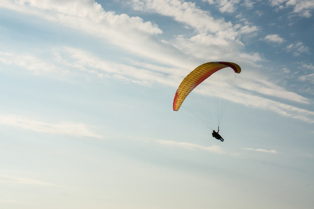 person flying on paraplane, cloudy sky on background