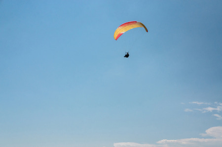 man flying on paraglider, blue sky on background