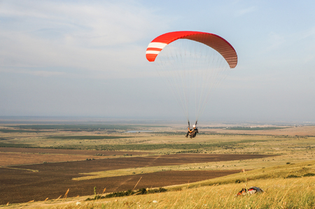 person flying on paraplane sky with clouds on background