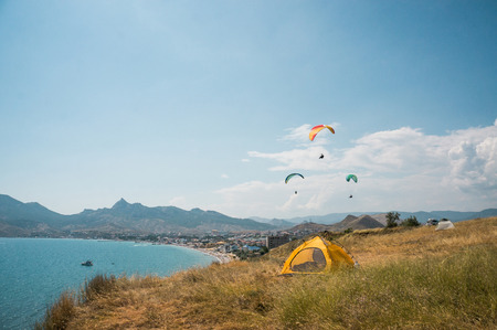 people flying on paragliders at sea, camping on foreground