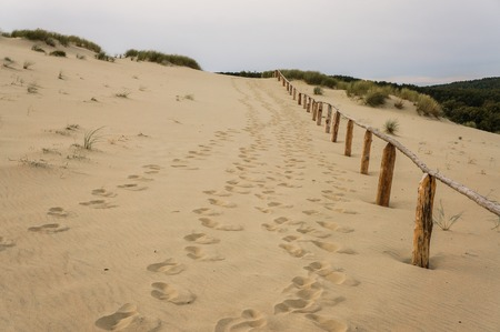 sendy beach with footprints and wooden fence Stock Photo