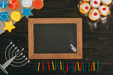 top view of frame, menorah, donuts and cookies with star of david on wooden tabletop, hanukkah celebration Stock Photo