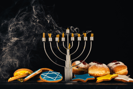 traditional jewish menorah for hanukkah celebration, doughnuts and cookies,  isolated on black