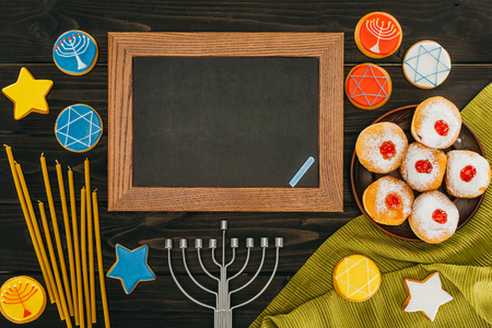 top view of blackboard in frame, menorah, donuts and cookies with star of david on wooden tabletop, hanukkah celebration
