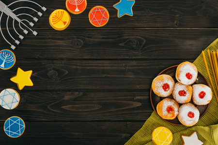 top view of menorah, donuts and cookies with star of david on wooden tabletop, hanukkah celebration Stock Photo