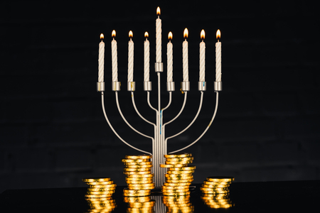 celebration with menorah, candles and Hanukkah gelt,  isolated on black