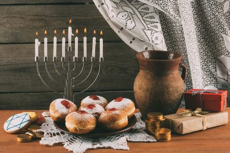 traditional jewish menorah, ceramic jug, Hanukkah gelt, gifts and donuts for hanukkah celebration  Stock Photo