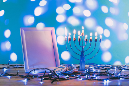 frame with copy space, traditional hanukkah menorah and cookies with bokeh blue lights on background