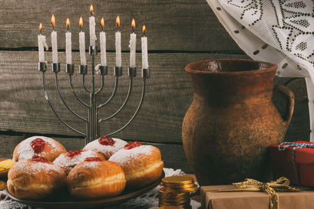 traditional jewish menorah, ceramic jug, gifts and donuts for hanukkah celebration