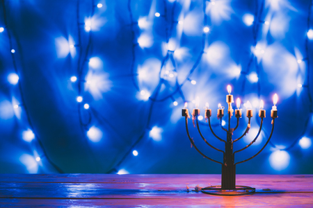 traditional jewish menorah with candles with bokeh blue lights on background