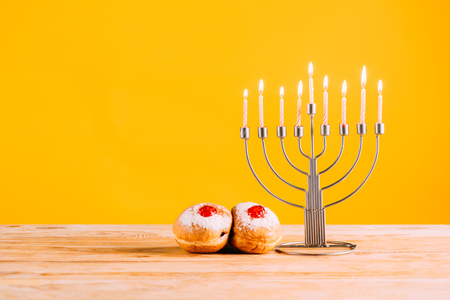 hanukkah celebrating with menorah and donuts on wooden tabletop on yellow