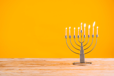 menorah with candles standing on wooden tabletop on yellow, hanukkah celebrating