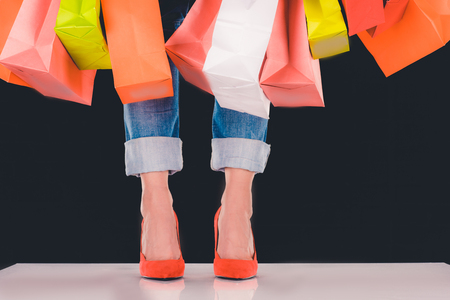 cropped view of woman with shopping bags, isolated on black