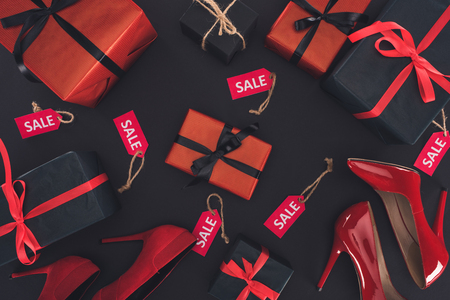 top view of red heels, presents and sale tags, isolated on black  Stock Photo
