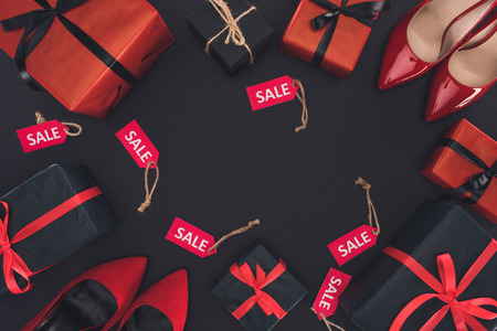 flat lay with red heels, presents and sale tags, isolated on black, black friday concept Reklamní fotografie - 90111585