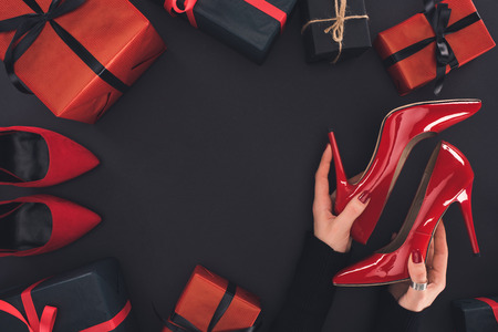 cropped view of woman holding red heels, isolated on black with presents and tags