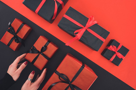 cropped view of woman holding gifts, on red and black Stock Photo