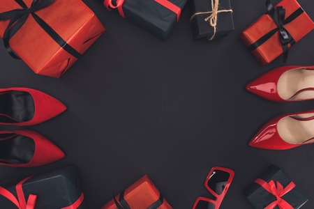 top view of red heels and presents, isolated on black with copy space