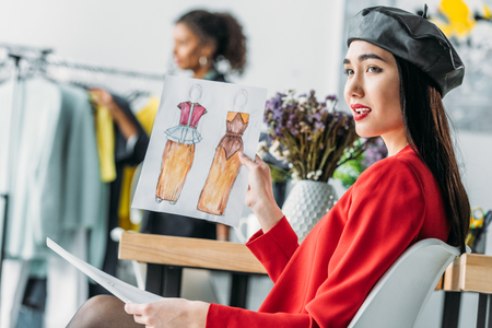 asian fashion designer with sketches