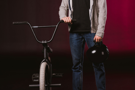 cropped shot of young cyclist holding helmet and standing with bmx bicycle in studio