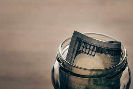 나무 탁상에 달러 지폐와 함께 유리 항아리 스톡 콘텐츠