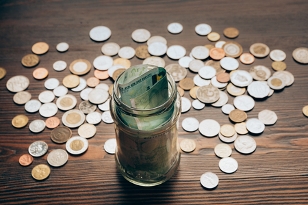 glass jar with banknotes on wooden tabletop with coins