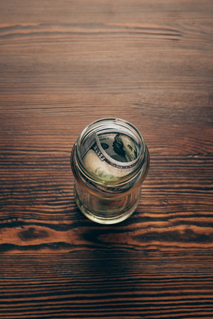 glass jar with dollar banknotes on wooden tabletop