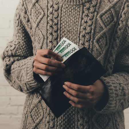 cropped view of woman in sweater holding wallet with euro banknotes