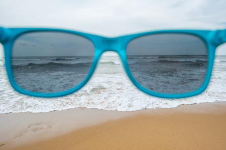 view of stormy sea through blue sunglasses